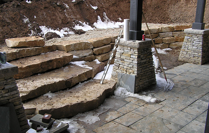 The steps and first four courses of the wall are set and backfilled with washed gravel.