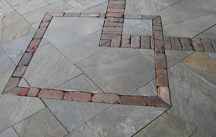 Used clay pavers are inlaid in the bluestone patio under the deck.