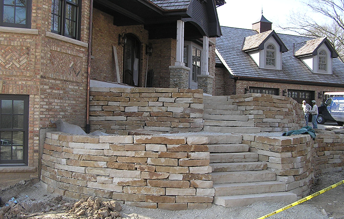 Retaining walls and steps of cut sandstone lead up to the front door.