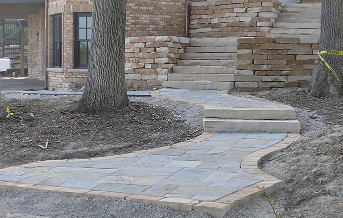 The front walk is natural Bluestone bordered with cut Sandstone chosen to match the walls.