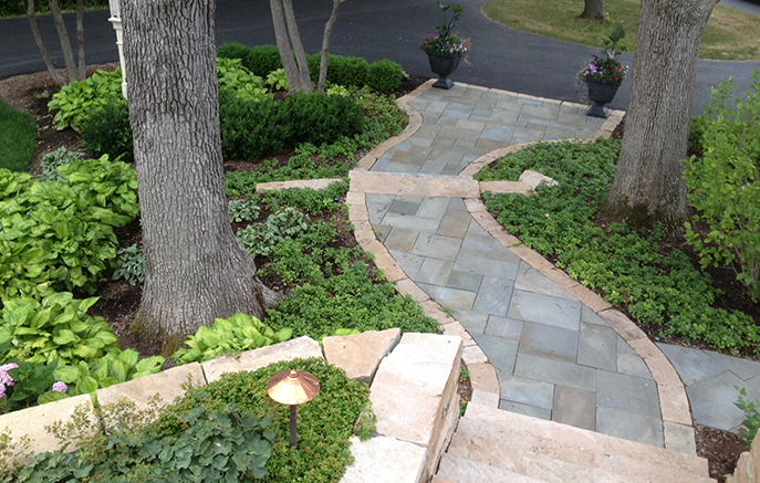 Shade-loving plantings line the front walk with their lush foliage.
