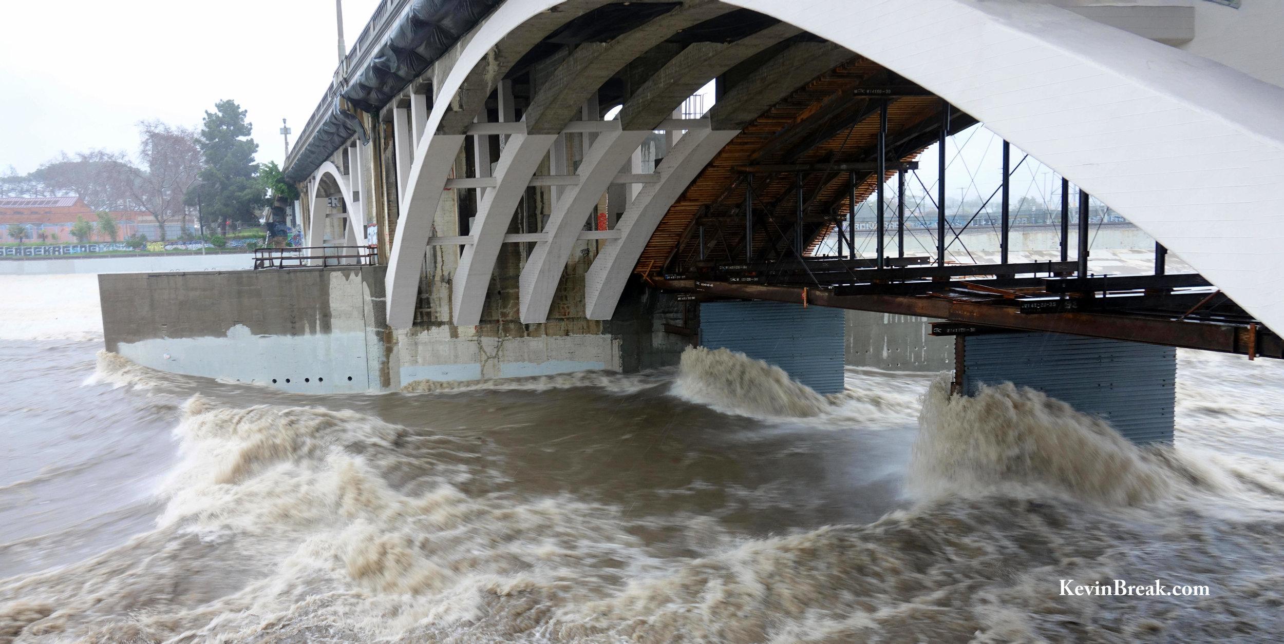 Rain storm waters flood underneath Spring Street bridge