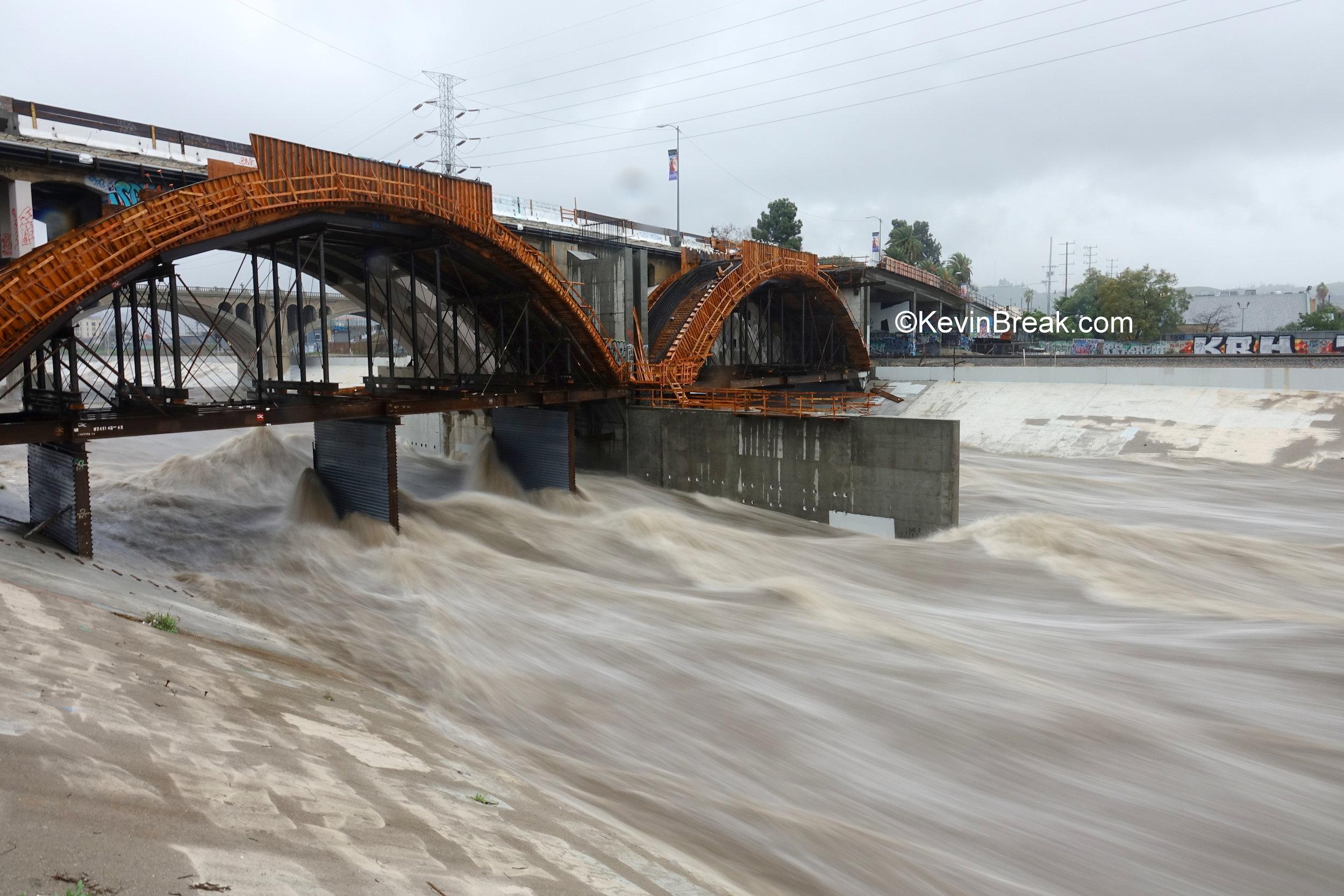Storm waters rage under Spring Street bridge