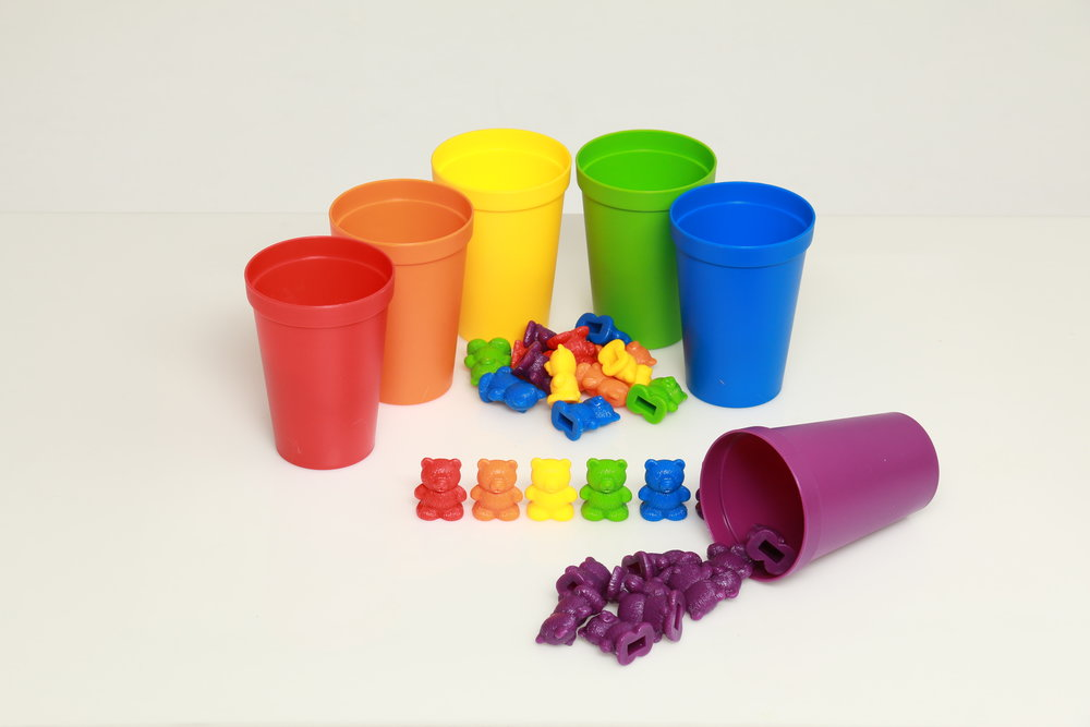 Plastic cups and mini plastic bears in a white background