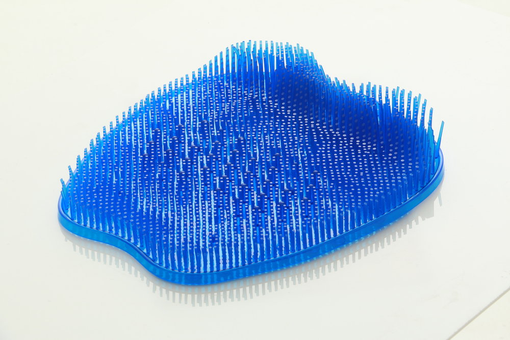 Blue shower foot scrubber on a white background