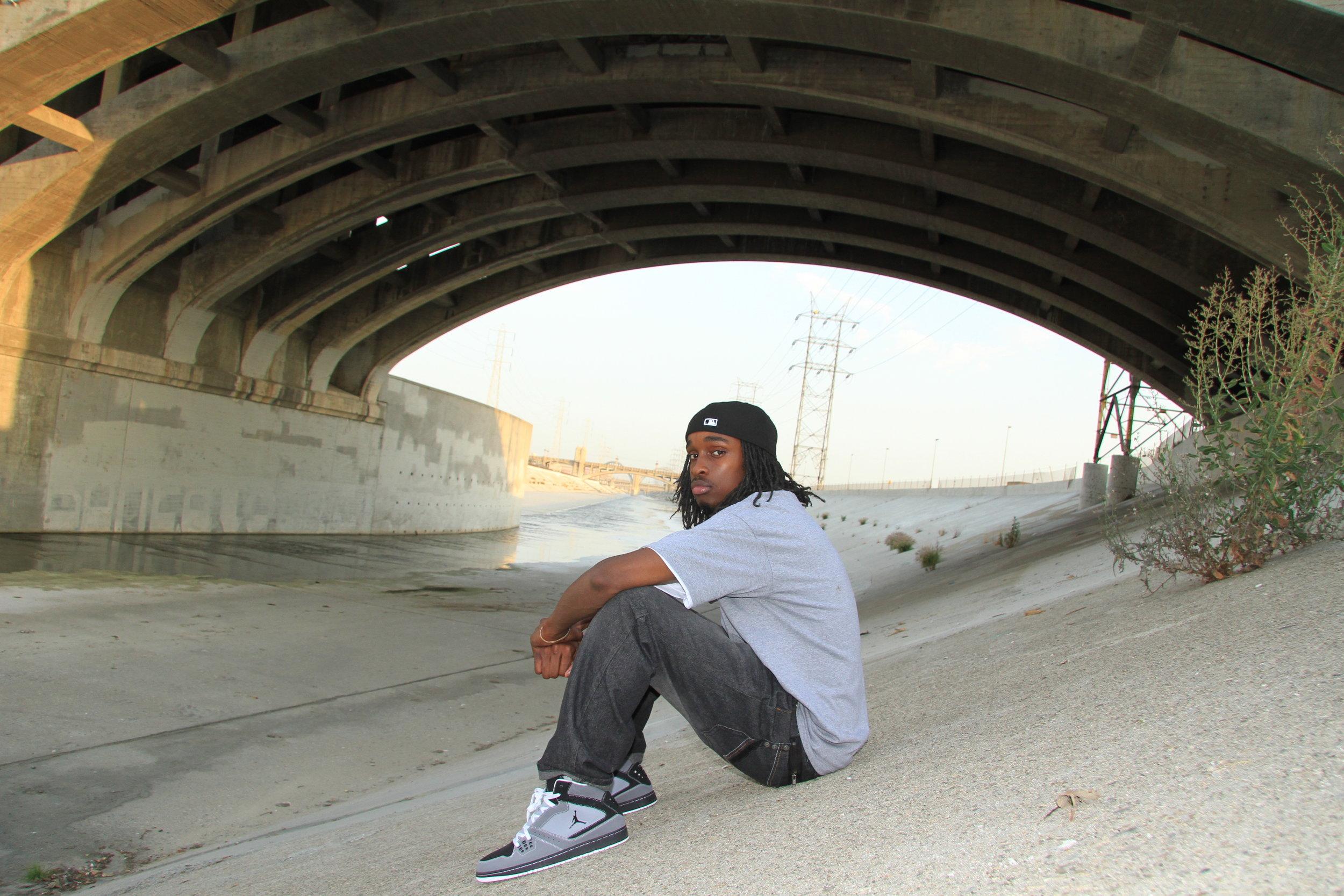 Musician posing shit sitting under the 1st street bridge