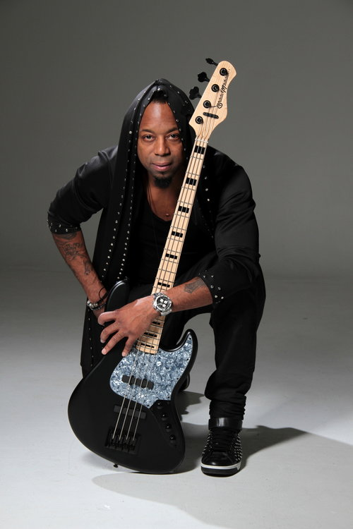 Music Artist posing with this black guitar in from of the white cove