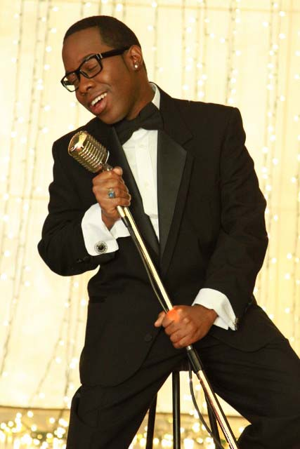 Singer in a tuxedo posing with a metal microphone