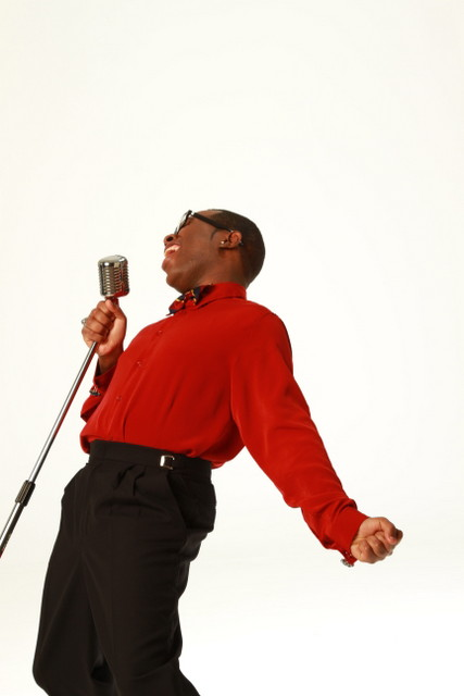 Musician in red long sleeve shirt singing into a metal standing microphone