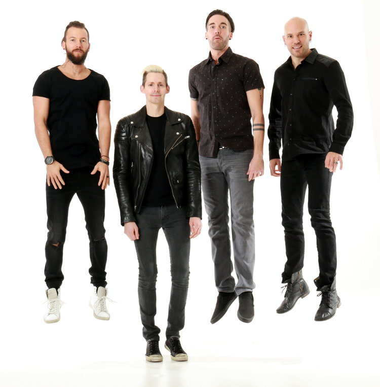 Band wearing all black posing together in front of the white cove