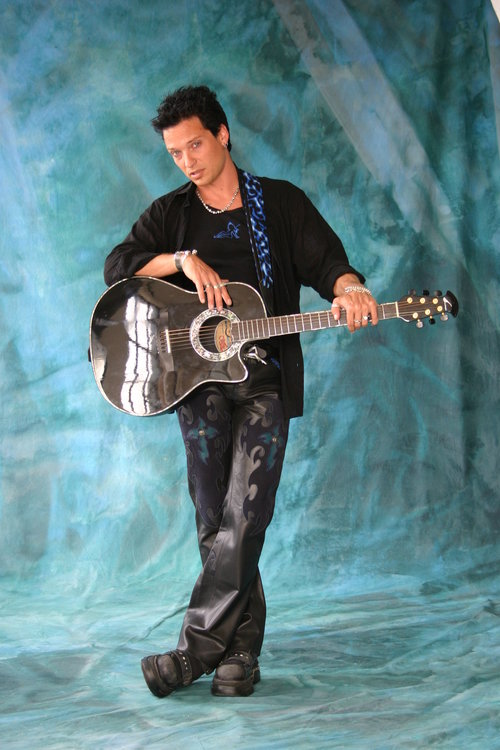 Musician posing with this acoustic guitar