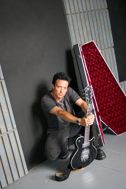 Musician posing with his guitar sitting down with a coffin in the background