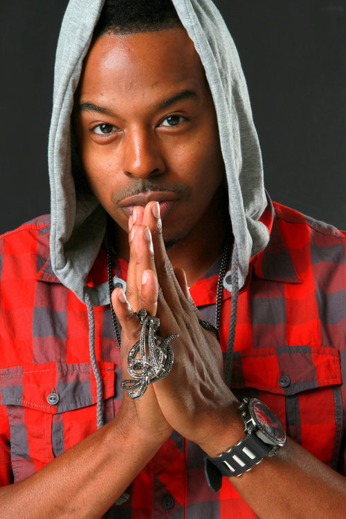 Music artist posing with his hands in a praying gesture