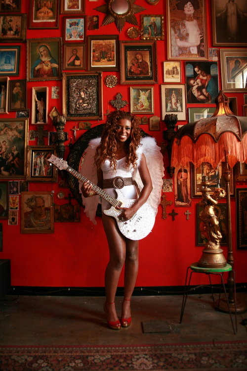 Guitarist posing with her guitar in front of the jesus wall