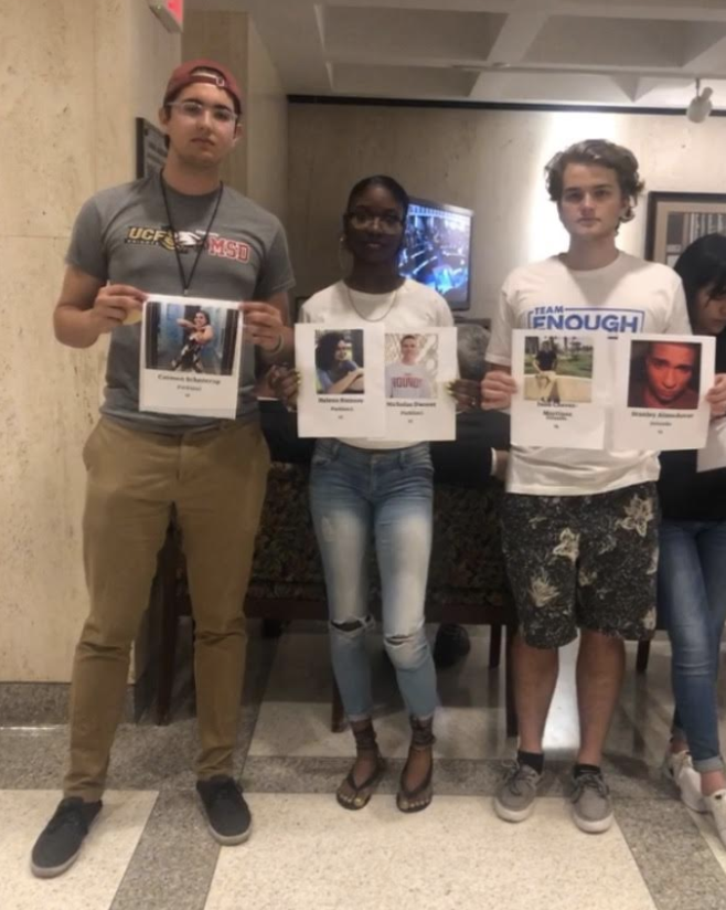 Robert joined Team ENOUGH members Aalayah Eastmond and Sam Sharf in visiting the Florida State Capitol to protest SB 7030 on arming teachers. He holds a photo of his sister, Carmen, who was killed in the Parkland shooting.