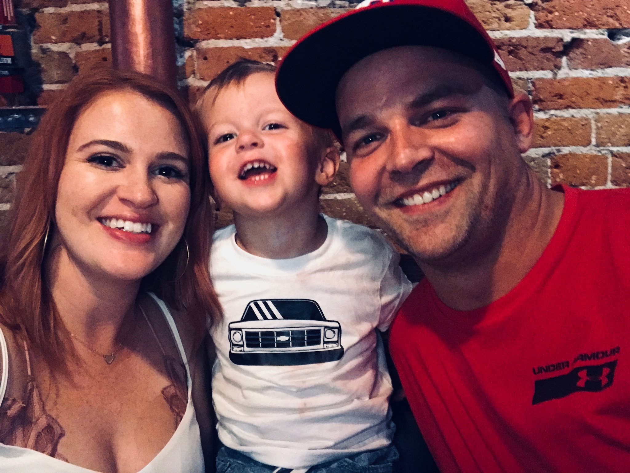 """Here we are at a bar in downtown Denver because our night did not go as planned at all. Lincoln is wearing his favorite """"t ruck shirt """" as he asks to wear daily."""