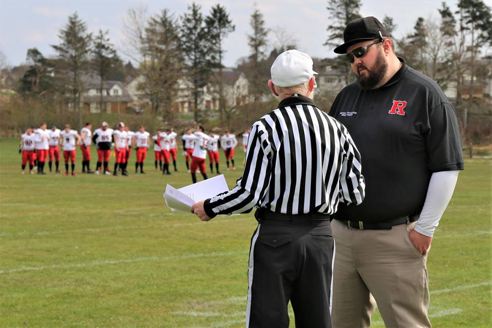 Head Coach Bryce Stevenson speaks with the Head Referee ahead of the game
