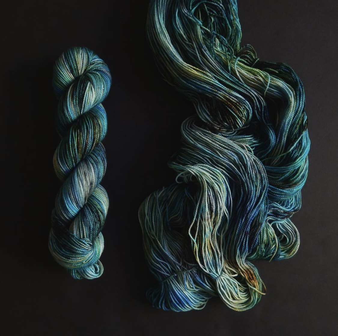 Two hanks of green & blue yarn sit side by side on a black background, one skeined and one unskeined; Photo by Tayler Earl of Fiber for the People®