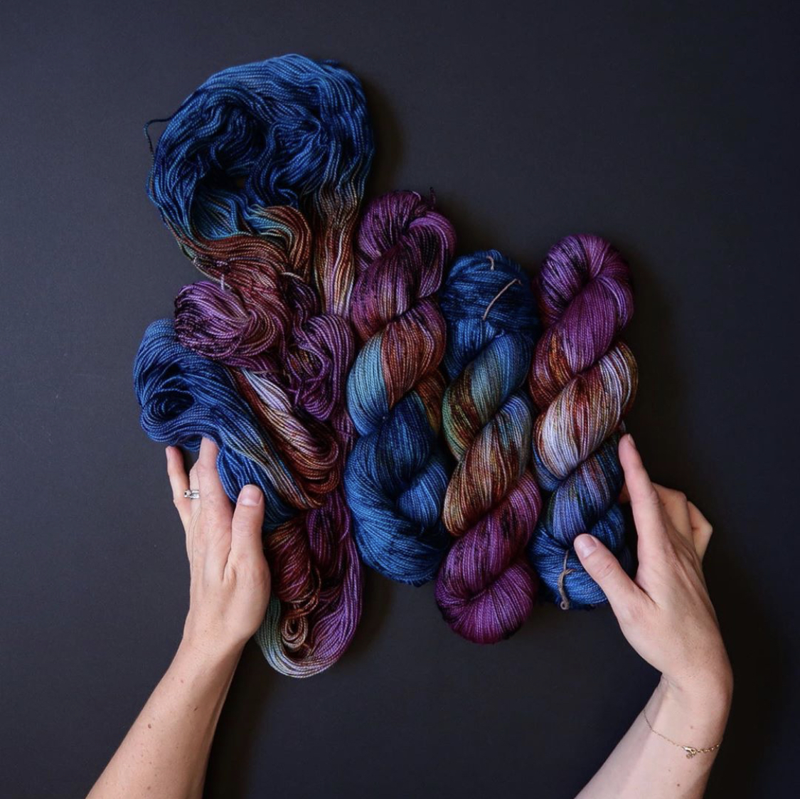 Tayler's hands embrace four hanks of blue & purple yarn, one hank unskeined and flowing; Photo by Tayler Earl of Fiber for the People®