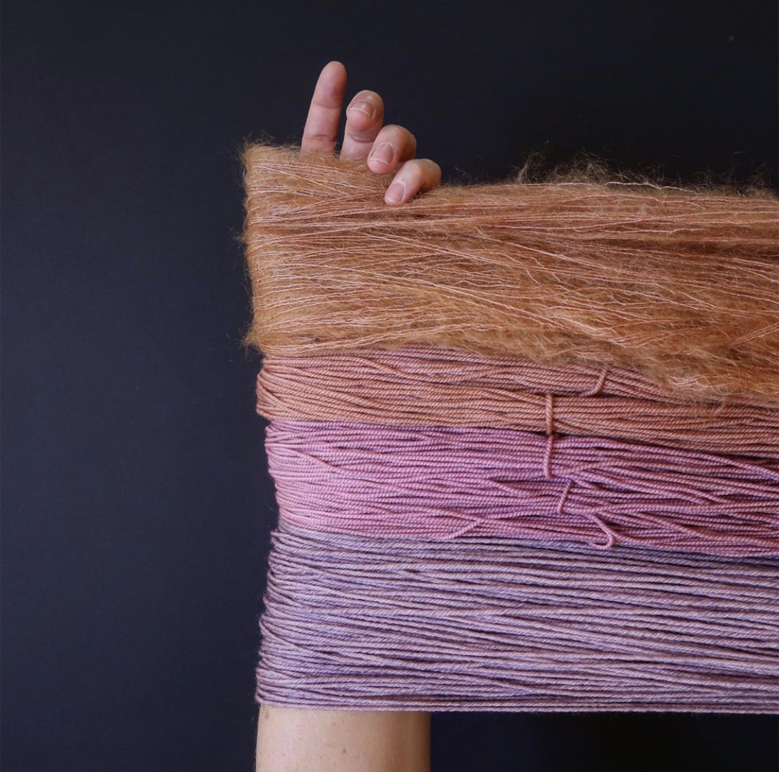 Four hanks of varying shades of pink yarn are stretched across Tayler's arm; Photo by Tayler Earl of Fiber for the People®