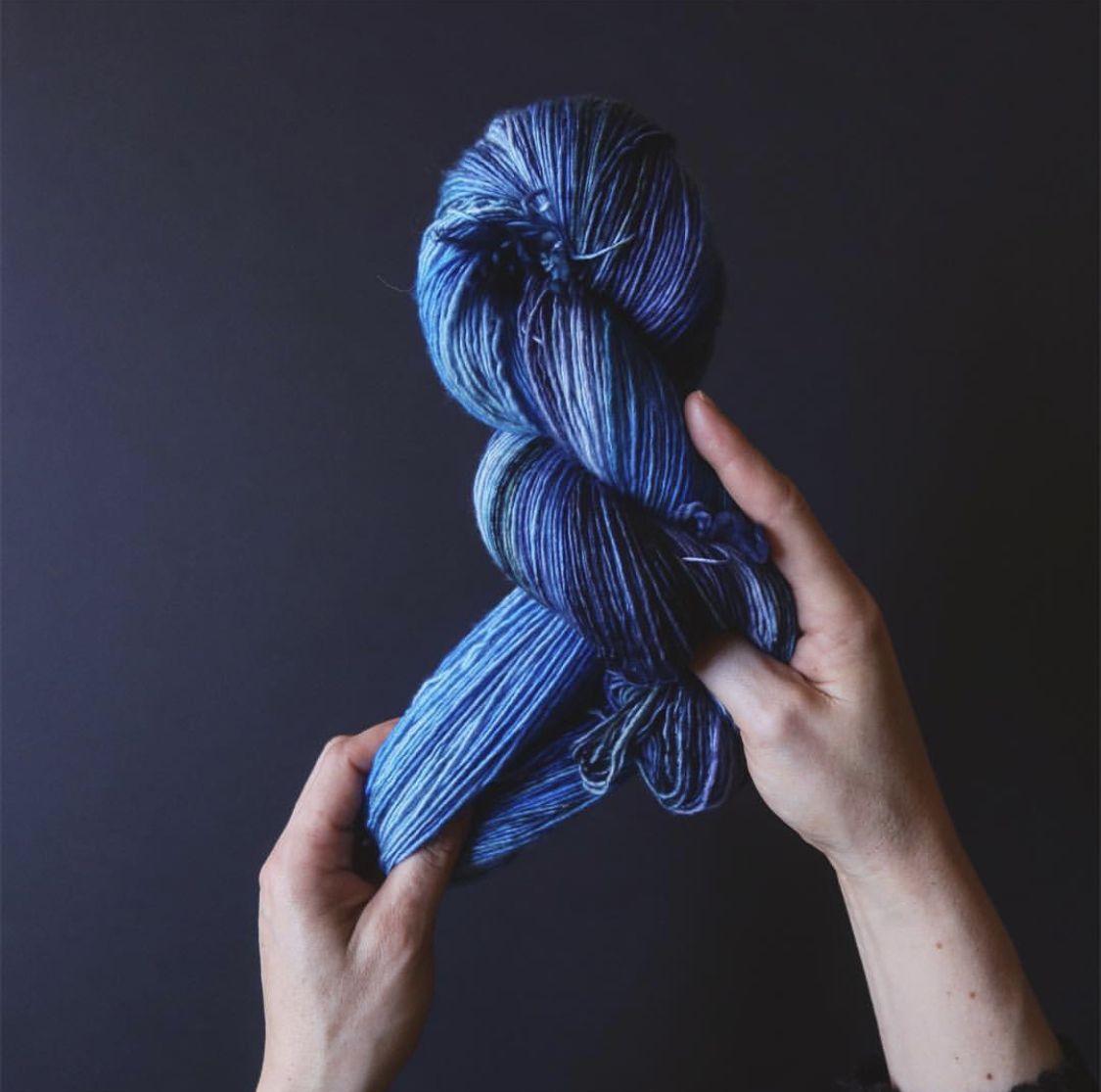 Tayler's hands stretch out a beautiful blue tonal skein; Photo by Tayler Earl of Fiber for the People®