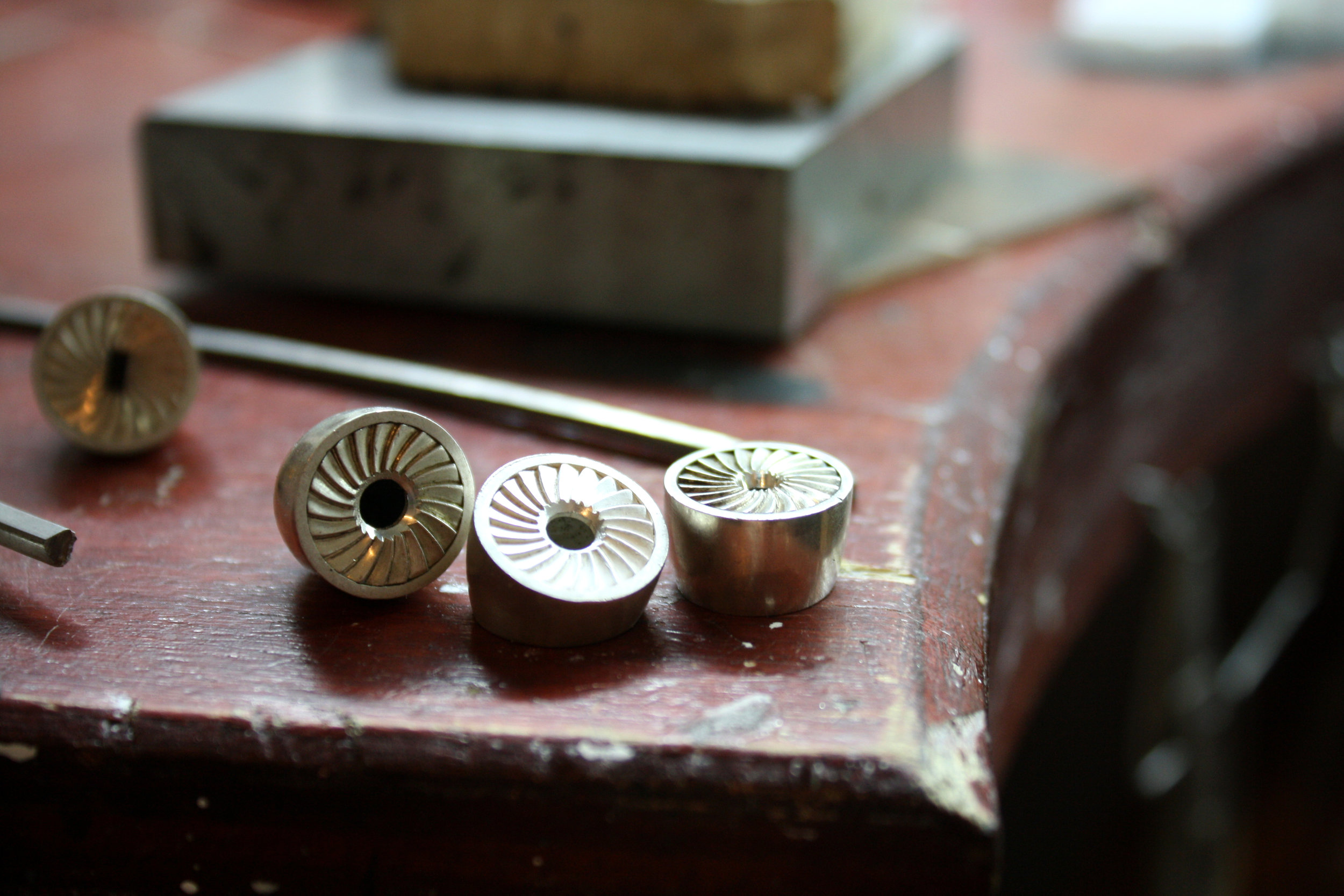 Silver turbine cufflinks on jewellers bench.jpg