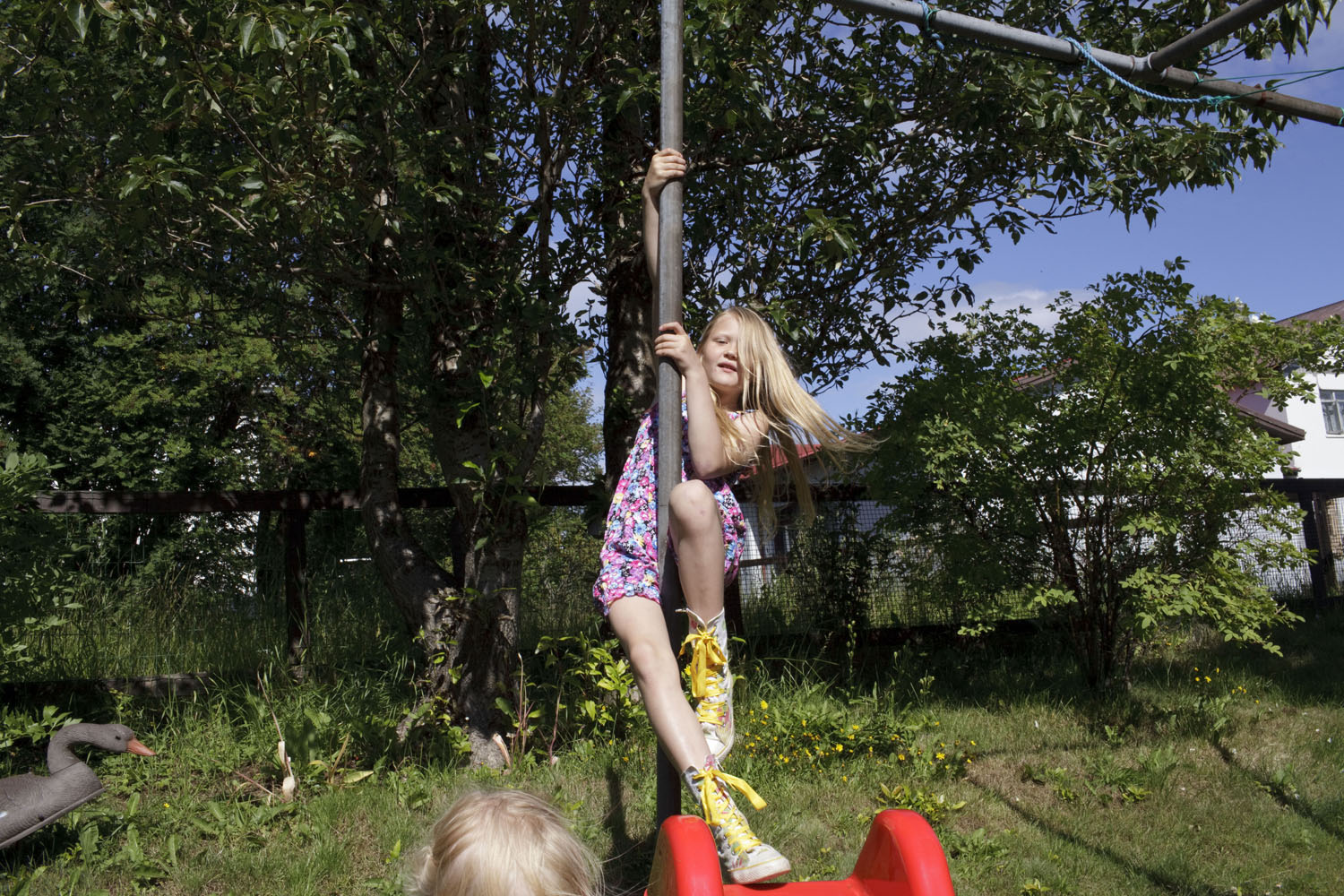 A girl plays in her backyard in Reykjavik after a morning at the pool with her mother and younger sister.