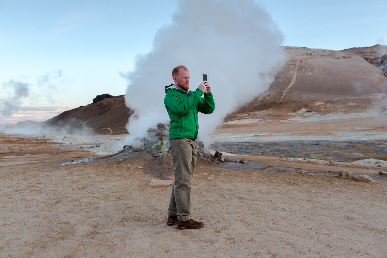 A tourist photographs steam escaping from a vent at Namafjall in in Lake Myvatn, a landscape covered with with mud pots and fumaroles.