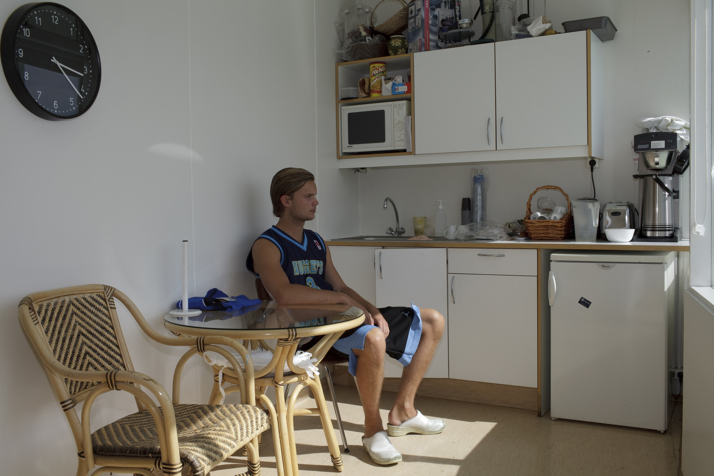A lifeguard sits in the break room at the local pool in Hveragerði.