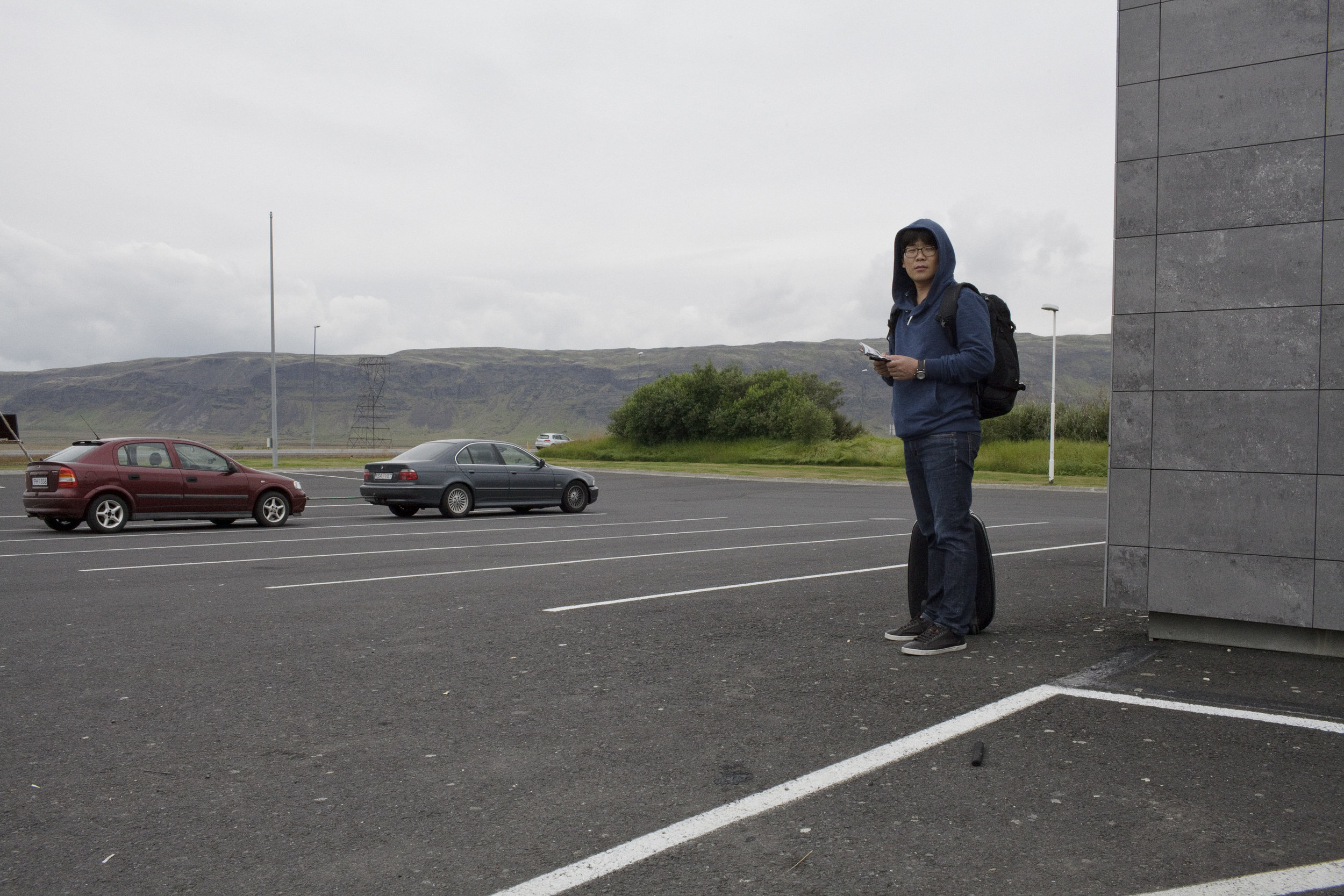 A tourist waits for the bus outside of a gas station in Hveragerdi.