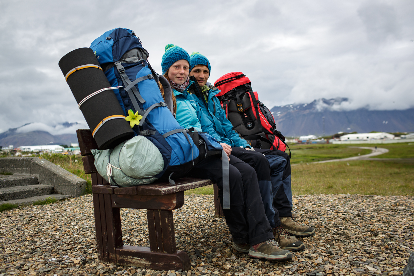 Two Polish backpackers hitch hiking their way across Iceland take a break on a bench in Hofn in southeastern Iceland.
