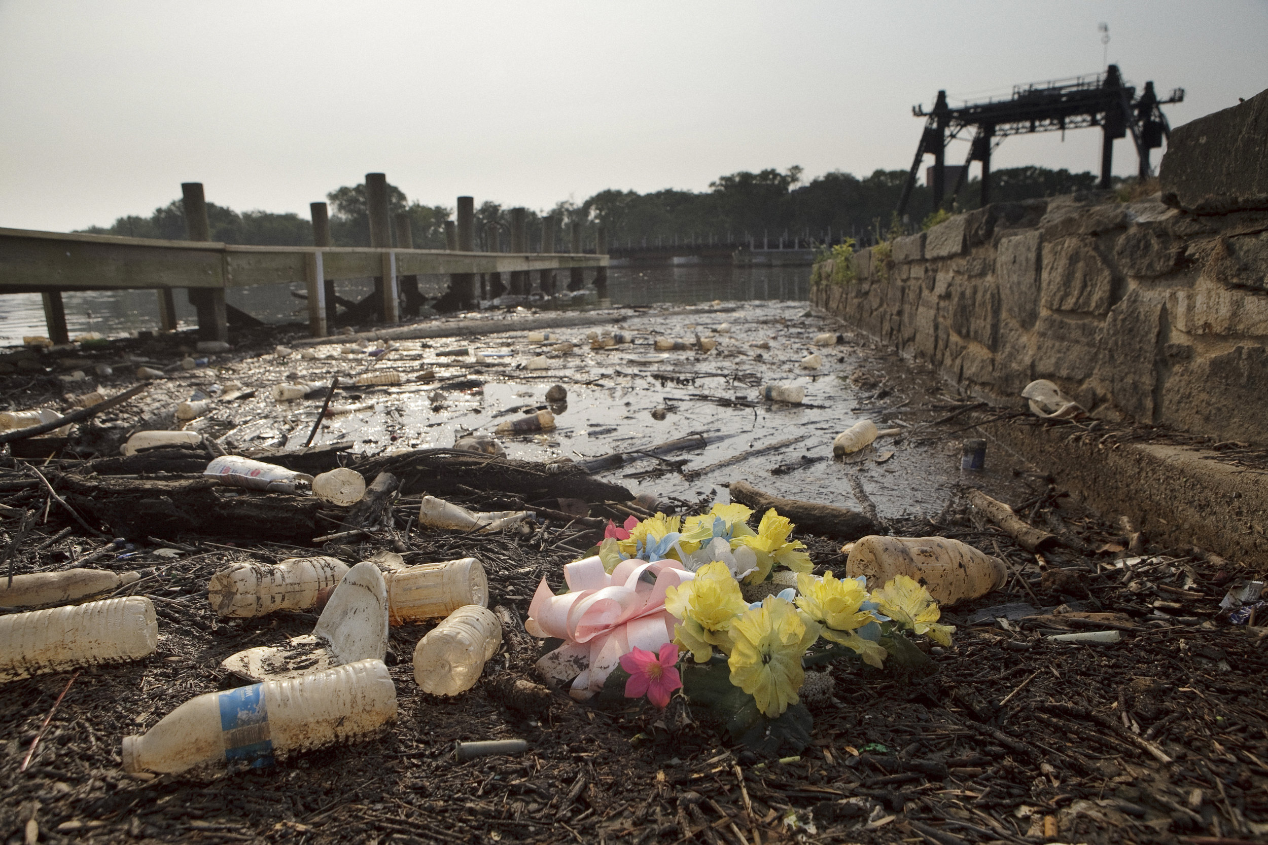 Rains often bring a great deal of trash to the surface of the river, here, what looks like a pristine funeral wreath is surrounded by washed up bottles and sticks.
