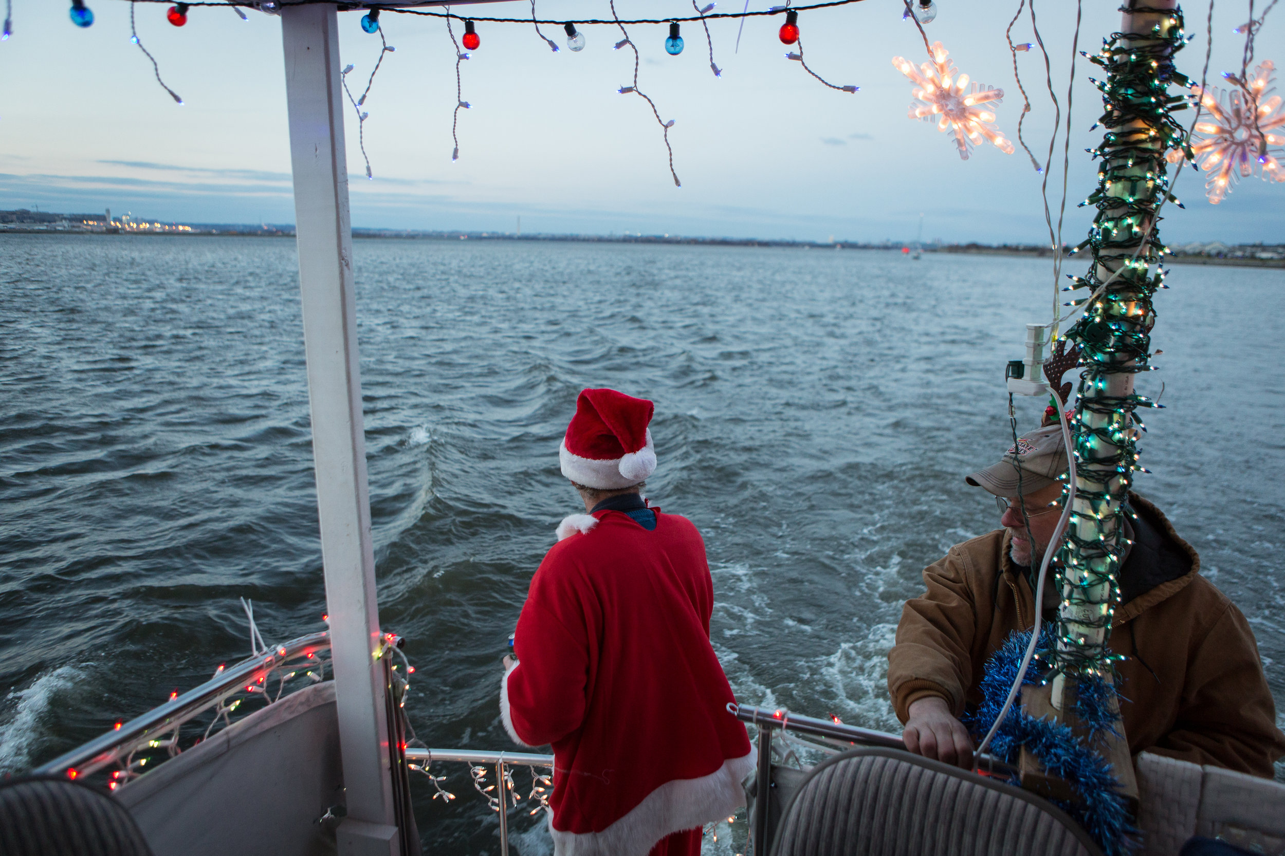 Greg Drenter, the commodore of the Eastern Power Boat Club, which is situated on the Anacostia River, rides in the parade of lights, an annual boat decorating competition.