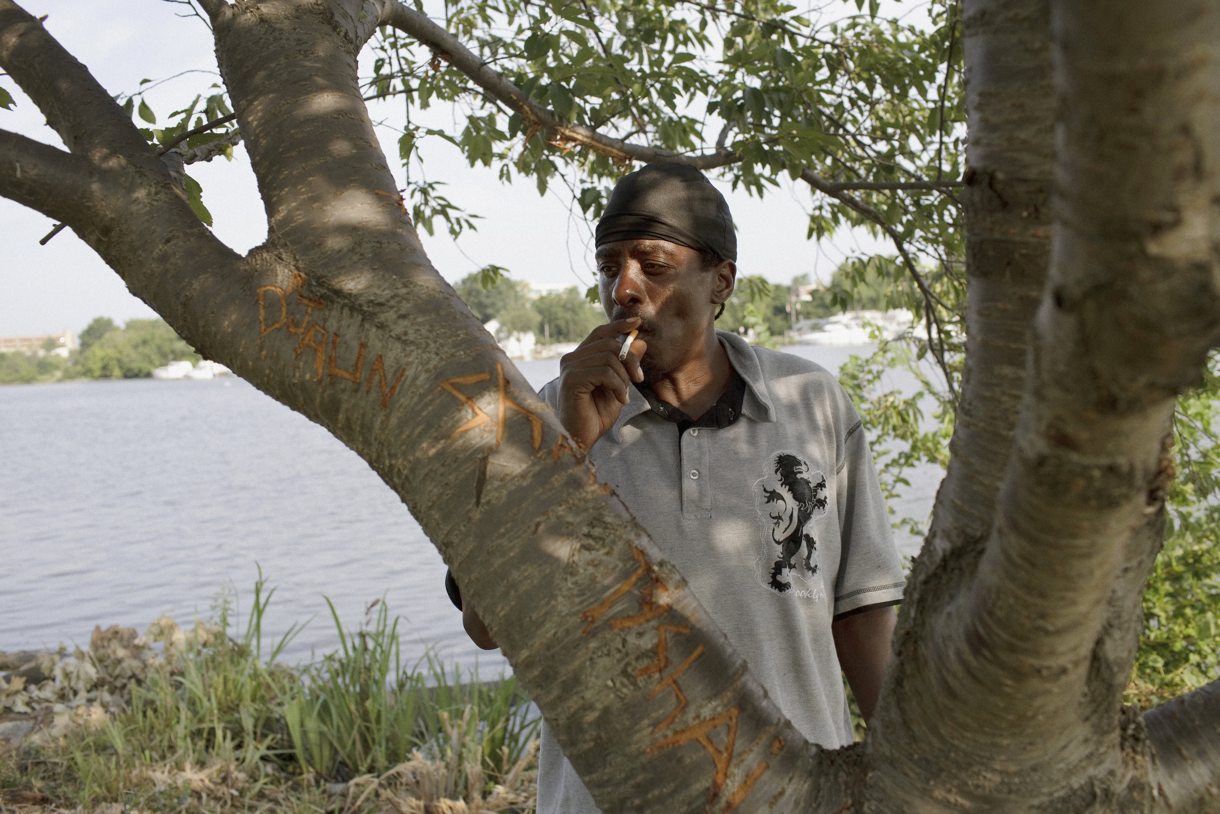 Wink, pictured here, and his best friend Earl routinely fish under this tree in Anacostia Park. Etched in the tree, D'Jaun is one of Wink's nine children, six of whom have their names carved here.