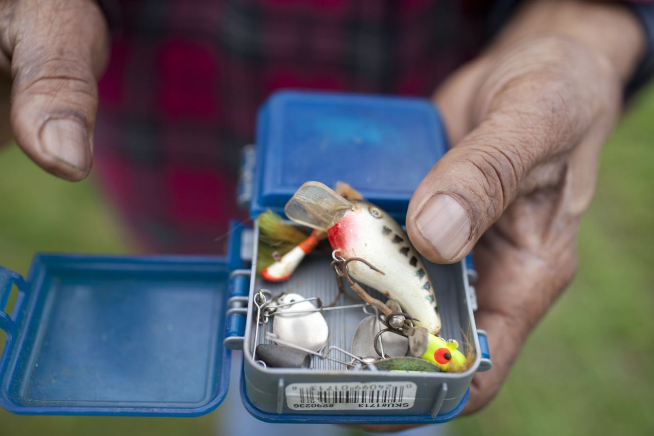 A man holds a tackle box as he fishes from the east bank of the Anacostia with his nephew. The two men didn't plan to keep their catch for themselves, but to share it with friends in need.