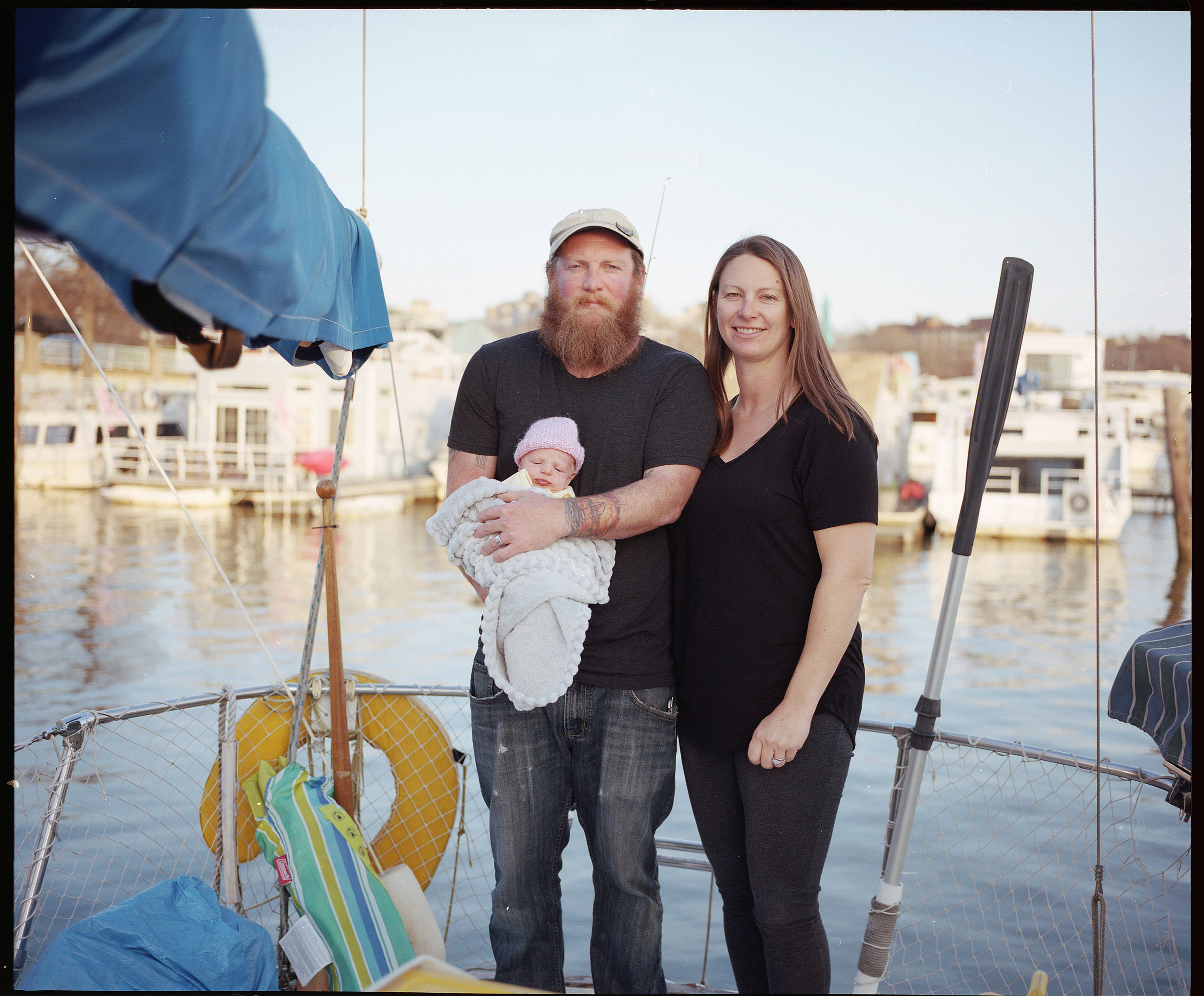 """Greg Whittier, Aubrey Andre and their then 17-day-old daughter Rue Constance aboard their sailboat Tenalach.  """"Gangplank is a family,"""" says Andre. """"Now we have an almost 5 month old baby, and she has been held and cared for by many neighbors. This childhood cannot be recreated in the current suburban neighbors, because here, everyday is a block party."""""""