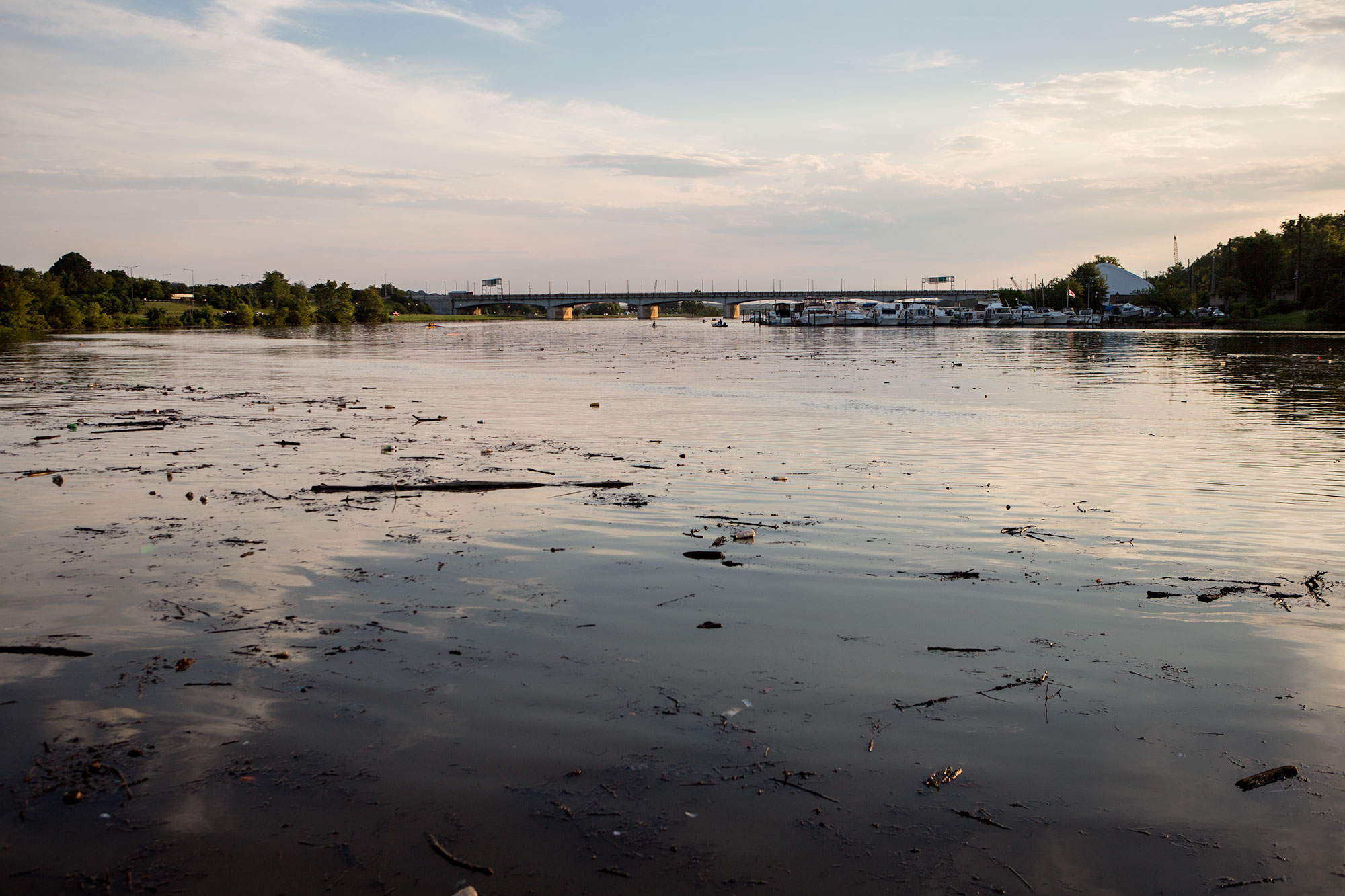 A quiet evening view of the Anacostia River in 2017 after a heavy rain, which stirred up debris in the river. The Seafarers clubhouse and the Pennsylvania Avenue bridge appear in the distance.