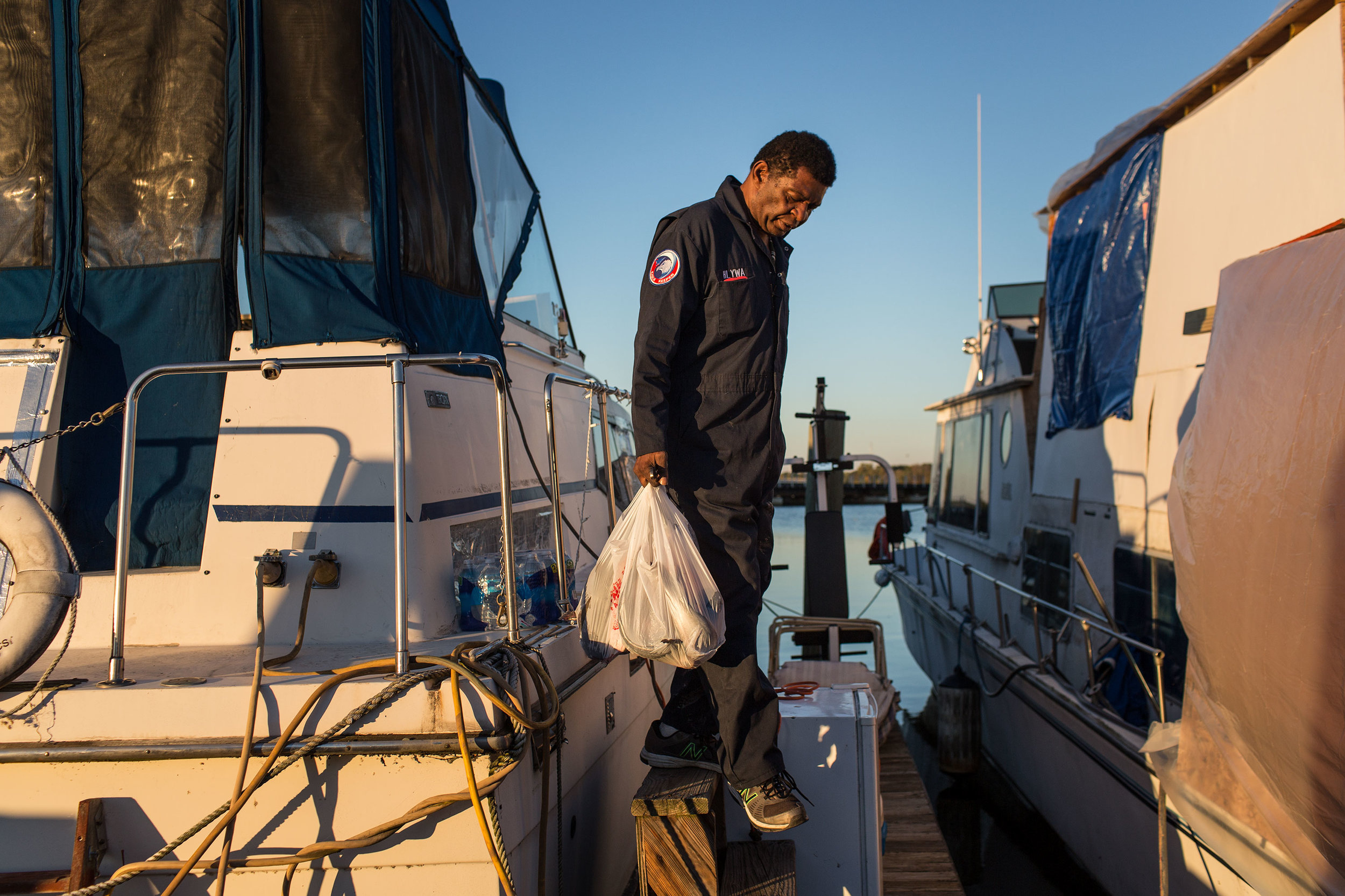 AJ Hall carries fish he caught from his boat,  The Raven .