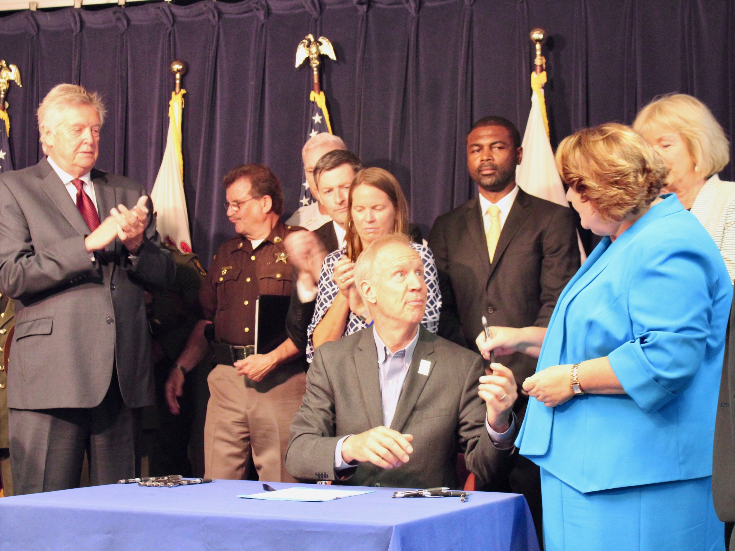 """Gov. Bruce Rauner hands a pen to state Rep. Kathleen Willis after signing the law on """"red flag"""" gun confiscation that she sponsored. (One Illinois/Ted Cox)"""