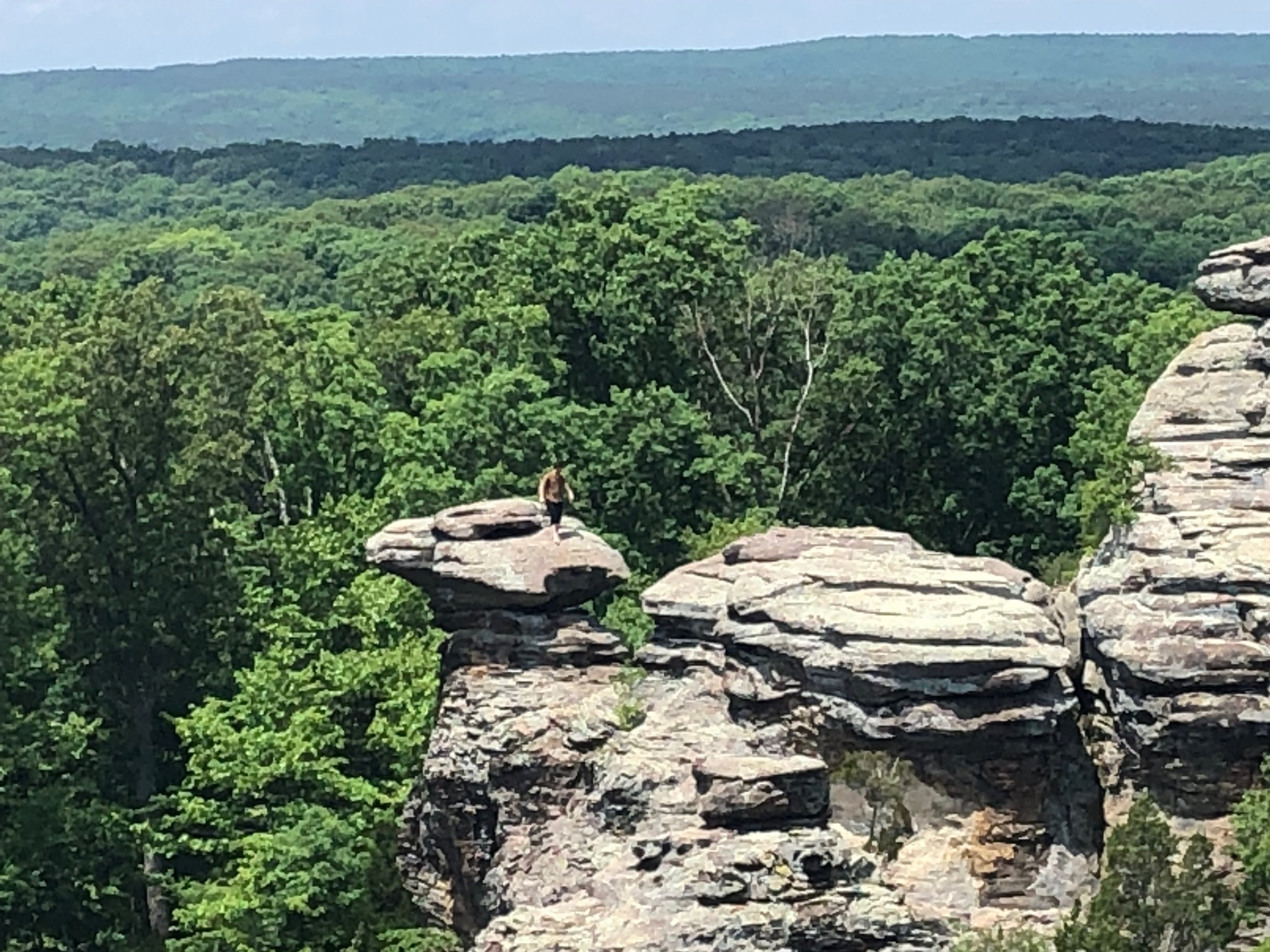 A sightseer stands atop Camel Rock at the Garden of the Gods in Shawnee National Forest in downstate Herod. (One Illinois/Ted Cox)