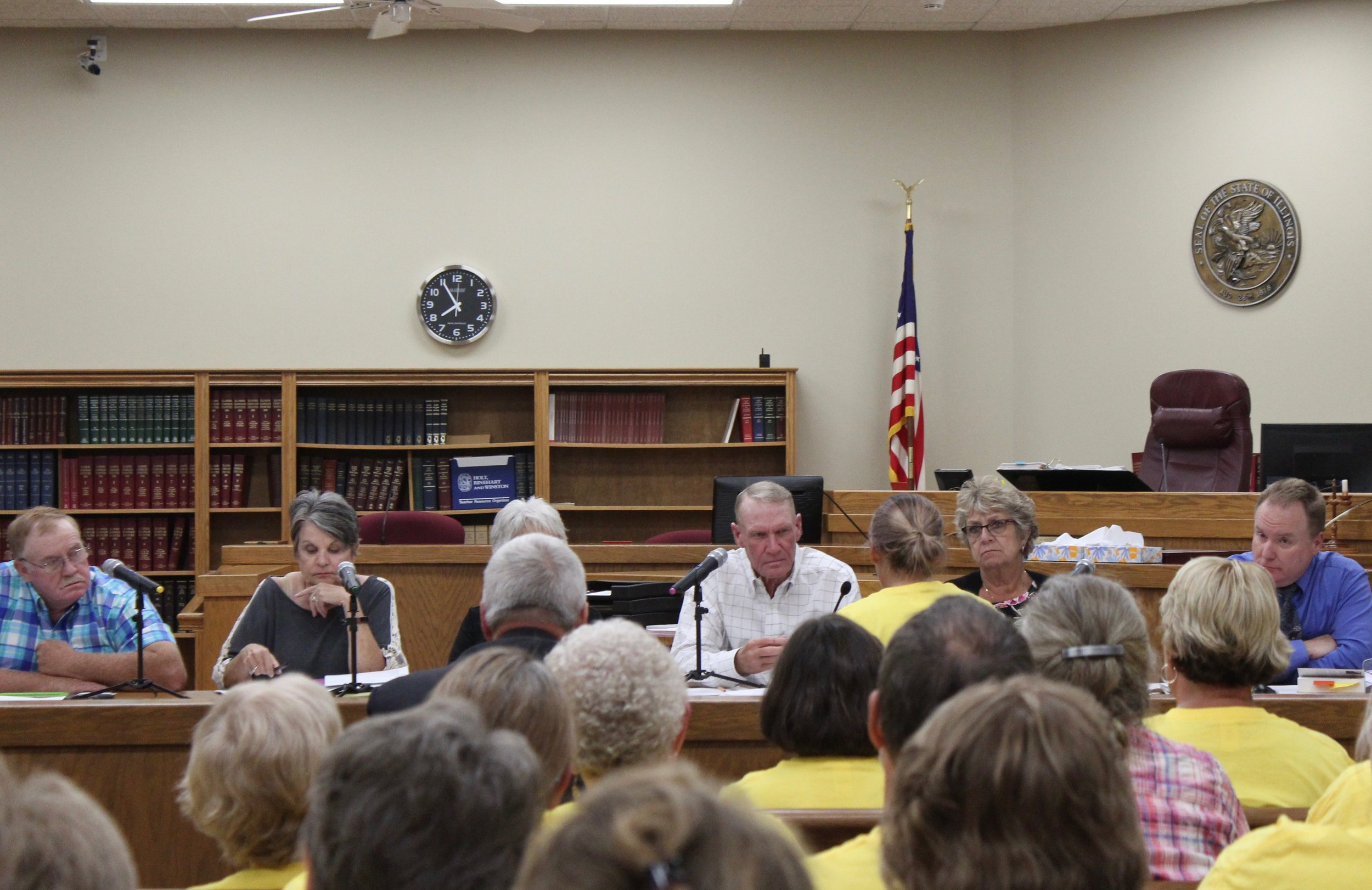 Andrea Rhoades testifies before the DeWitt County Board, with Chairman David Newberg at center. (One Illinois/Ted Cox)