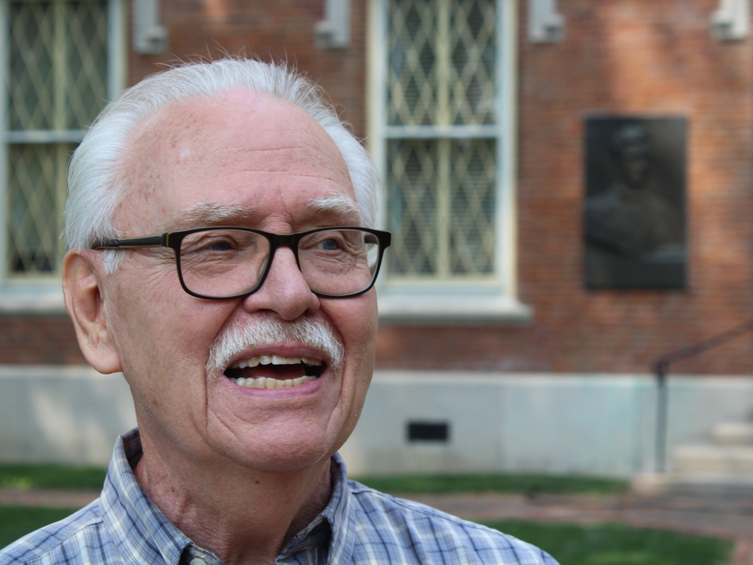 Owen Muelder talks in front of a Lincoln plaque on the east side of Old Main at Knox College, where Abraham Lincoln's debate with Stephen Douglas took place. (One Illinois/Ted Cox)
