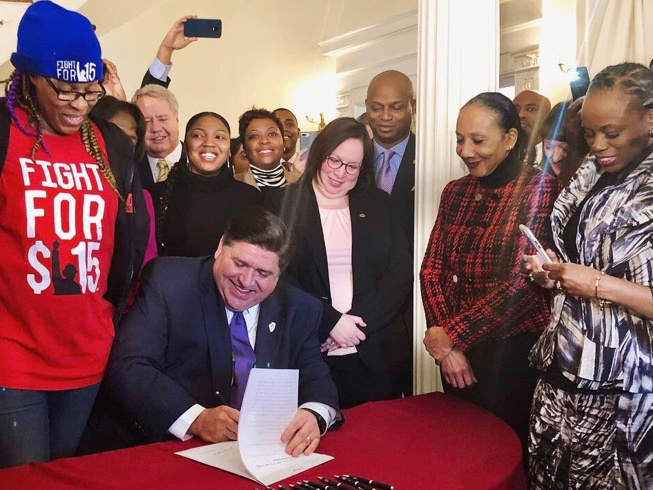 Gov. J.B. Pritzker signs a $15-an-hour minimum wage into law at the Governor's Mansion Tuesday. (Twitter/GovPritzker)