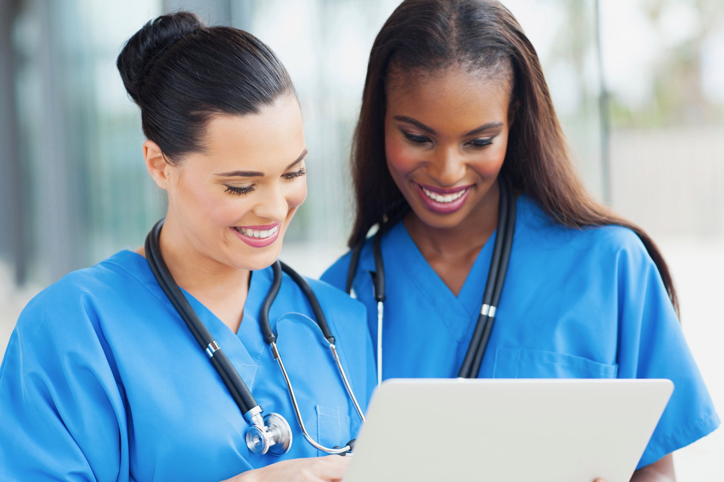 Nurses consult over a laptop. (Shutterstock)