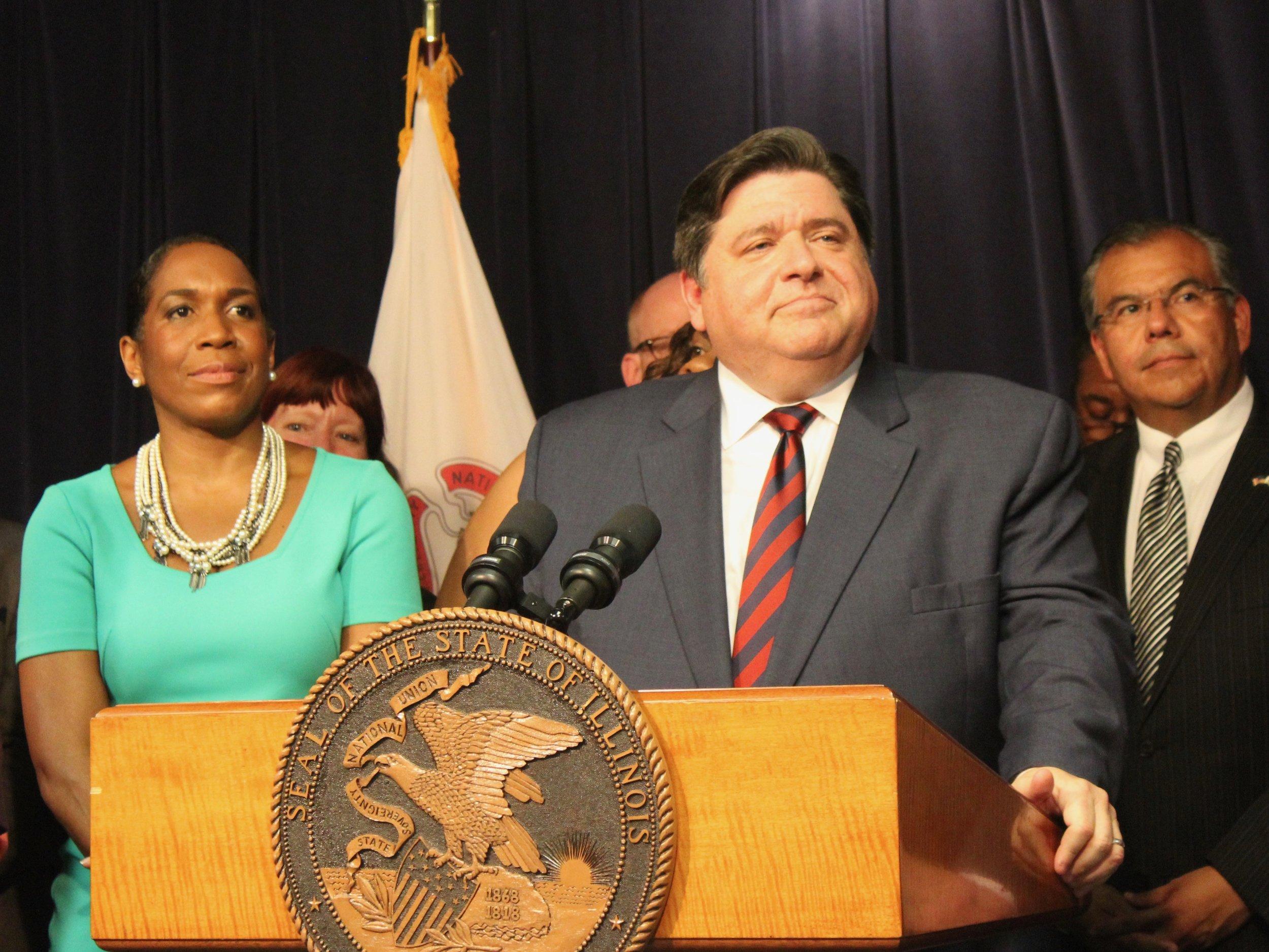 Gov. Pritzker is backed by Lt. Gov. Stratton after signing a balanced budget and a set of new tax brackets at the Thompson Center Wednesday. (One Illinois/Ted Cox)