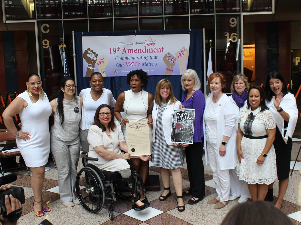 Women led by U.S. Sen. Tammy Duckworth, Lt. Gov. Juliana Stratton, and state Sen. Melinda Bush, all at center, brandish a proclamation declaring Monday to be Women's Right to Vote Day in Illinois at the Thompson Center. (One Illinois/Ted Cox)