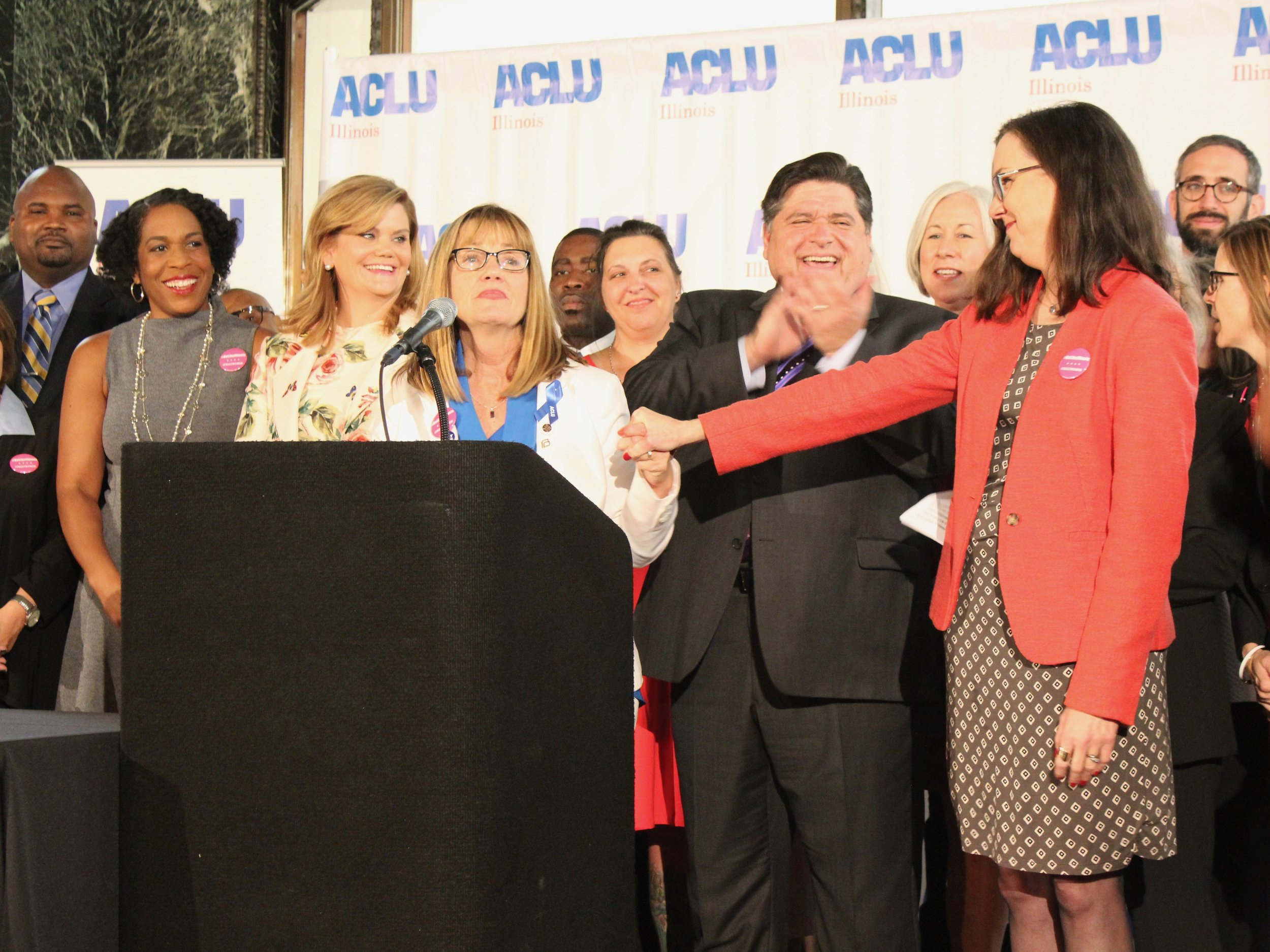 Lead General Assembly sponsors Sen. Melinda Bush and Rep. Kelly Cassidy hold hands in unity as Gov. Pritzker applauds ahead of signing the Reproductive Health Act into law. (One Illinois/Ted Cox)