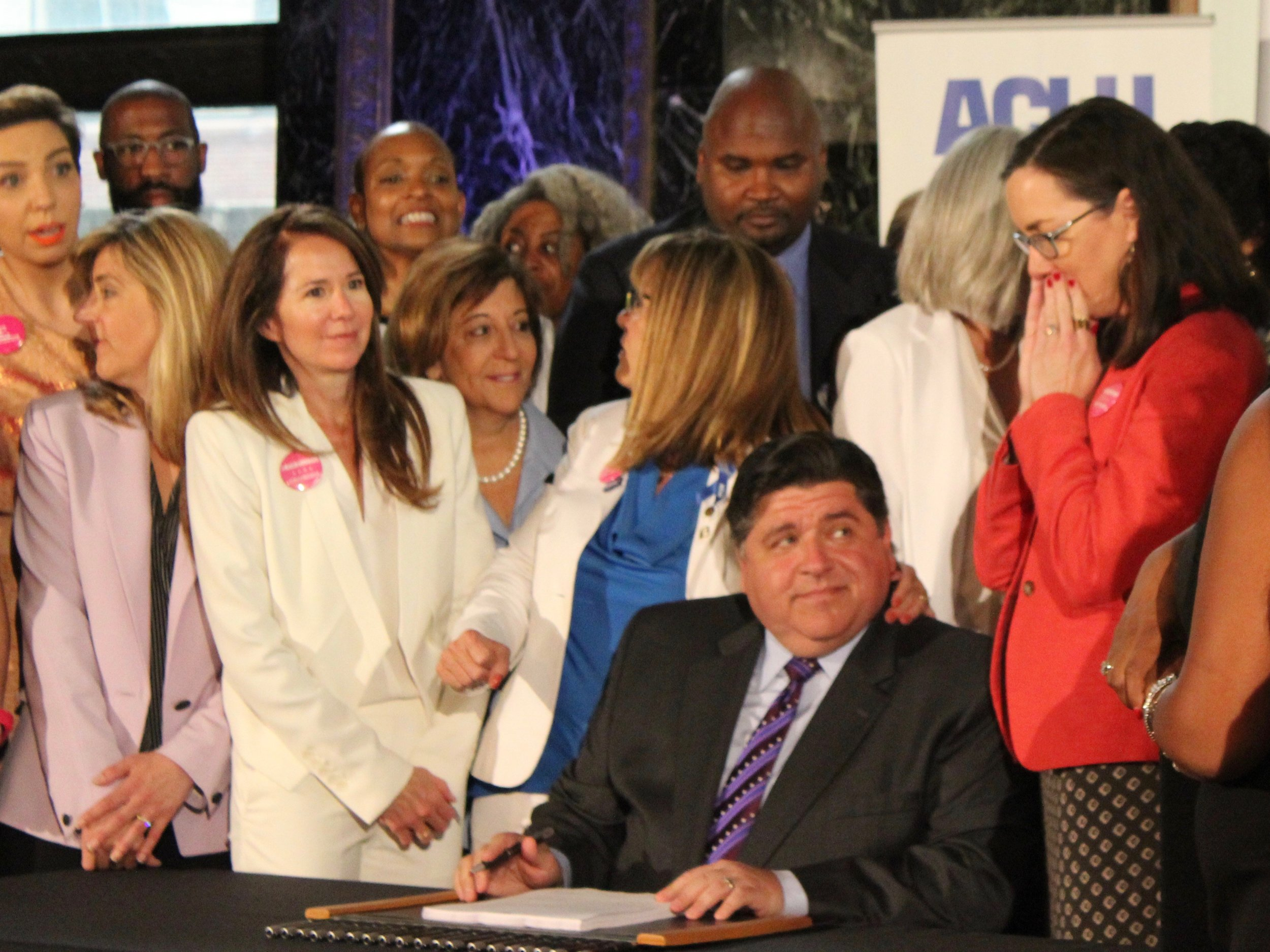 Backed by Sen. Bush and Rep. Cassidy, Gov. Pritzker prepares to sign the Reproductive Health Act into law. (One Illinois/Ted Cox)