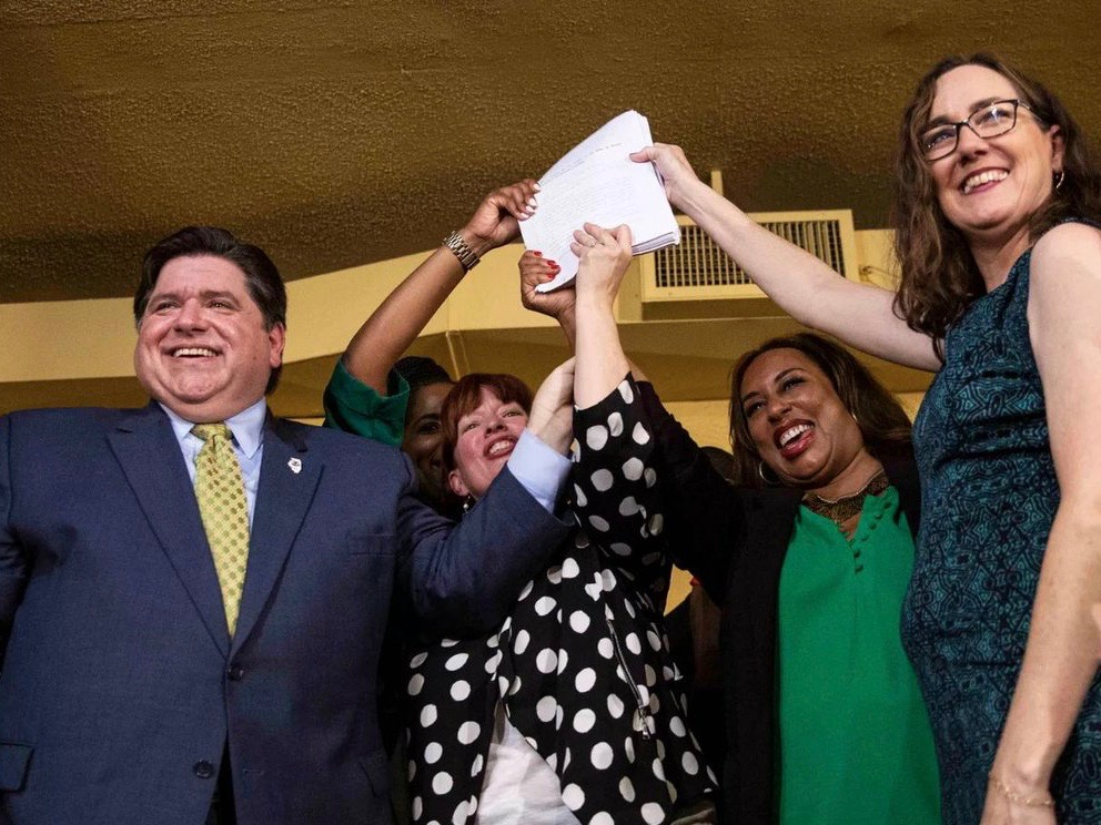 Gov. Pritzker brandishes the signed legalization law, joined by state legislators Jehan Gordon-Booth, Heather Steans, Toi Hutchinson, and Kelly Cassidy. (Twitter/Jim Roberts)
