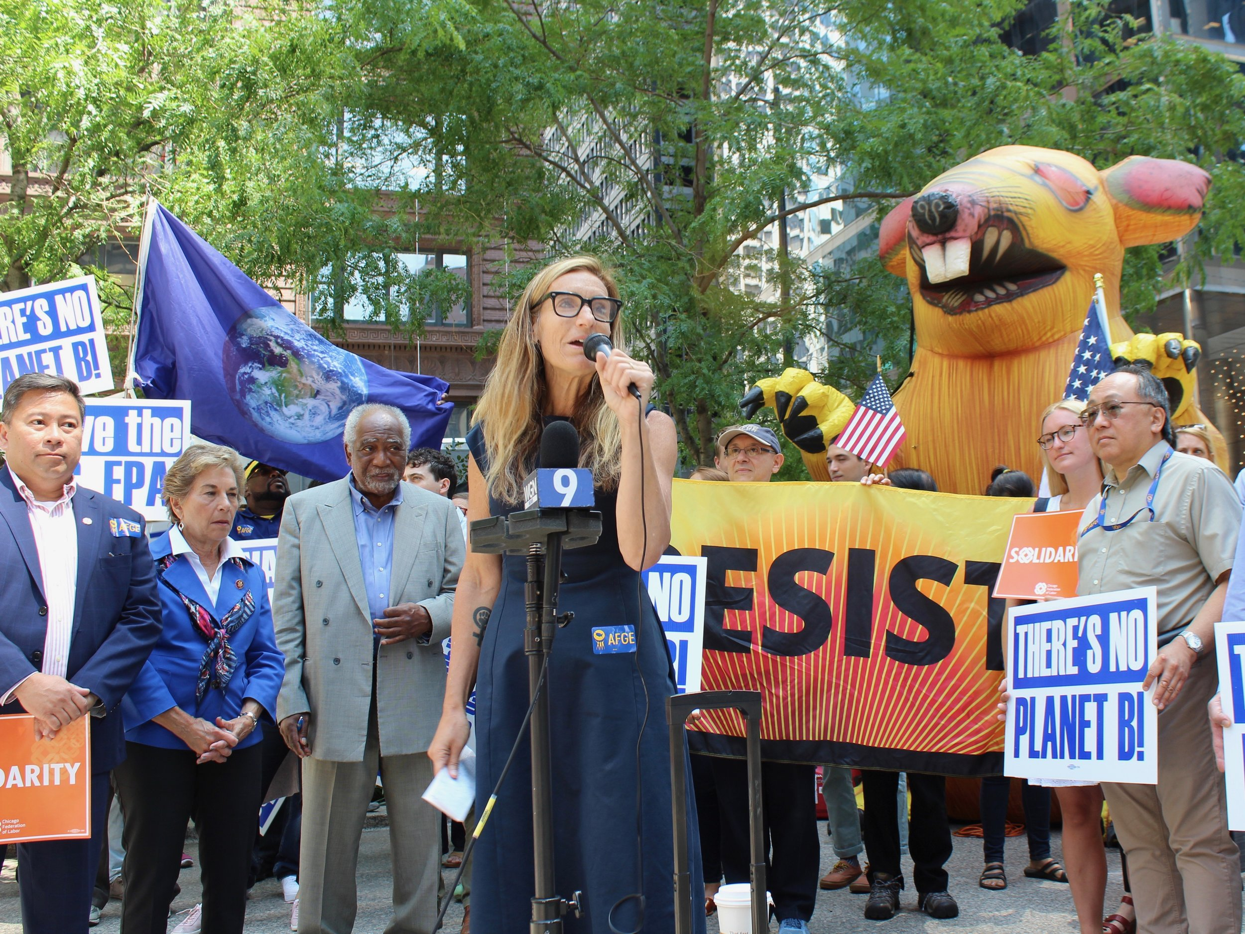 "Backed by U.S. Reps. Jan Schakowsky and Danny Davis (left) and the inflatable Scabby the Rat (right), EPA union leader Nicole Cantello decries what she calls ""an illegal directive"" on agency employees. (One Illinois/Ted Cox)"